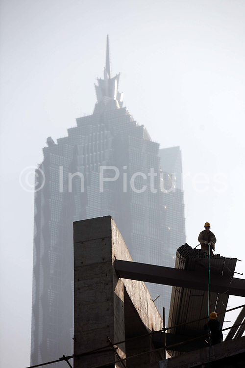 Construction workers operate on a scaffolding in front of the Jin Mao Hyatt in Shanghai, China on 18 December, 2009.  Shanghai is on its way of becoming one of the world's most important financial centers.