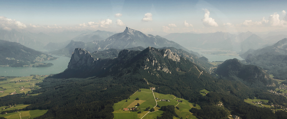 The view from Thalgau into the Salzkammergut, showing the full beauty of this landscape - the Mondsee on the left, then Drachenwand, Schober and Frauenkopf, with the famous Schafberg sitting on top of them, finalizing the view with the Wolfgangsee on the right.<br /> <br /> This shot was taken from the window of a Piltus Porter PC-6, used to take skydivers to altitude.