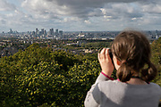 A young girl looking through binoculars at the City of London from Severndroog Castle on the 6th October 2019 in London in the United Kingdom. Severndroog Castle is a folly situated in Oxleas Wood, on Shooters Hill in south-east London in the Royal Borough of Greenwich. It was designed by architect Richard Jupp, with the first stone laid on 2 April 1784.