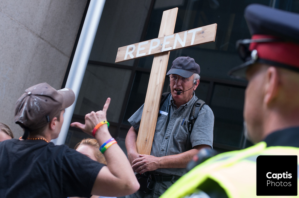A participant yells at a religious protester while a police officer stands near by. August 24, 2014.