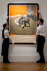 © Licensed to London News Pictures. 14/09/2012. LONDON, UK. Two members of Sotheby's staff adjust Francis Bacon's 'Study for a Bullfight No. 1' est. £30,000-50,000 as the New Bond Street auction house prepares for a sale of 'Old Master, Modern and Contemporary Prints'. The auction, set to take place on the 19th of September 2012, features nearly 200 masterful works artists including Andy Warhol, Lucian Freud and Francis Bacon. Photo credit: Matt Cetti-Roberts/LNP
