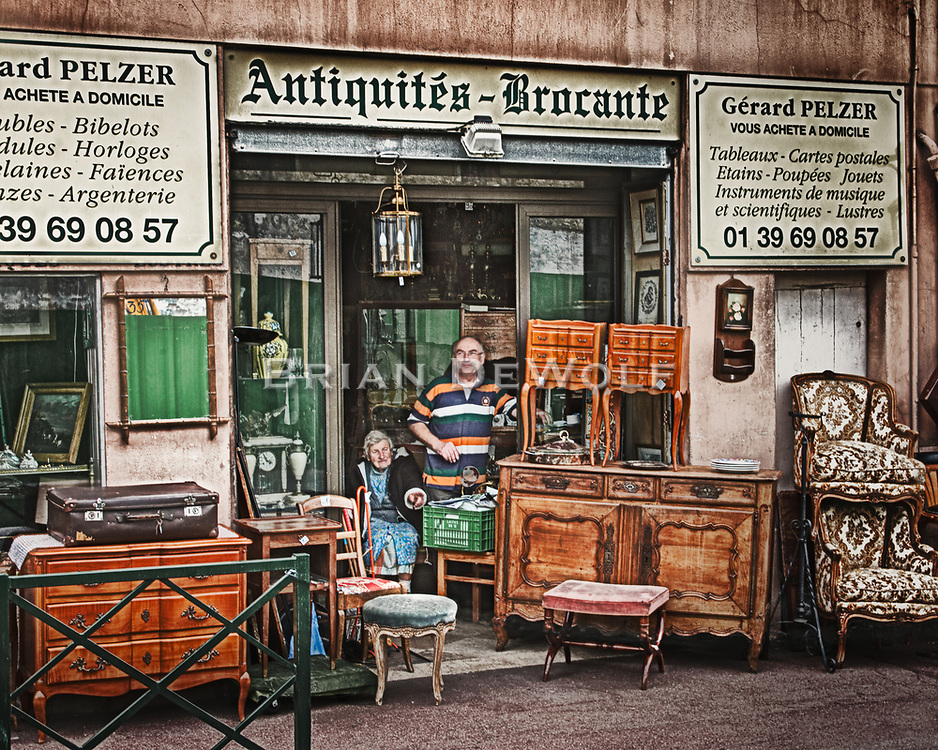 Antique merchants, a mother and son, watch traffic from their store front in Bougival, France. They were most pleased when they were told I wanted to photograph them.  Many times I've received less enthusiasm.  Aspect Ratio 1w x 0.8h