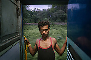 On the last evening before arrival, a man hangs out of the train's open door.<br /> Inside the Dibrugarh-Kanyakumari Vivek Express, the longest train route in the Indian Subcontinent. It joins Kanyakumari, Tamil Nadu, which is the southernmost tip of mainland India to Dibrugarh in Assam province, near the border with Burma.