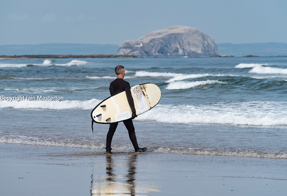 Senior male surfer carries  surfboards to sea at Belhaven Beach, Bass Rock in distance, East Lothian, Scotland, United Kingdom