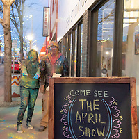Tasha Nez, left, and Keanu Mitchell, right toss powdered colors into the air on the sidewalk outside of the Art123 Gallery during the Second Look on Second Street art walk in Gallup on Tuesday.