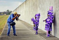 29 August 2015. Lower 9th Ward, New Orleans, Louisiana.<br /> Hurricane Katrina 10th anniversary memorial.<br /> Photographer Eric Waters with L/R; Tia (7 yrs) and Takiera (9 yrs) Augustin of the 9 Red Hawk Mardi Gras Indians at the levee wall which gave way a decade earlier. <br /> Photo credit©; Charlie Varley/varleypix.com.