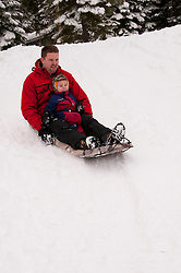 California, Lake Tahoe: Child and father enjoy snow play with sled at North Lake Tahoe Regional Park.  Photo copyright Lee Foster.  Photo # cataho107507