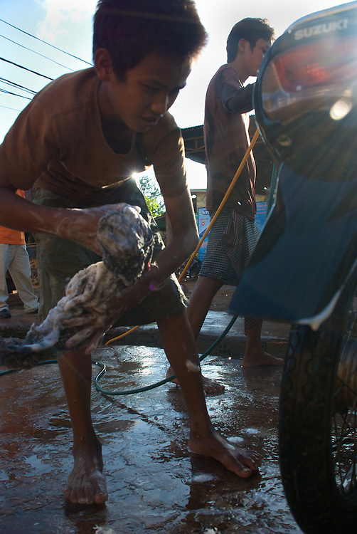 A fourteen-year old boy washes a motorcycle at a local car wash in Siem Reap, Cambodia where he is currently employed after dropping out of school to help support his family.  He commutes from outside the city to work, because there are few job opportunities in the village where he lives.