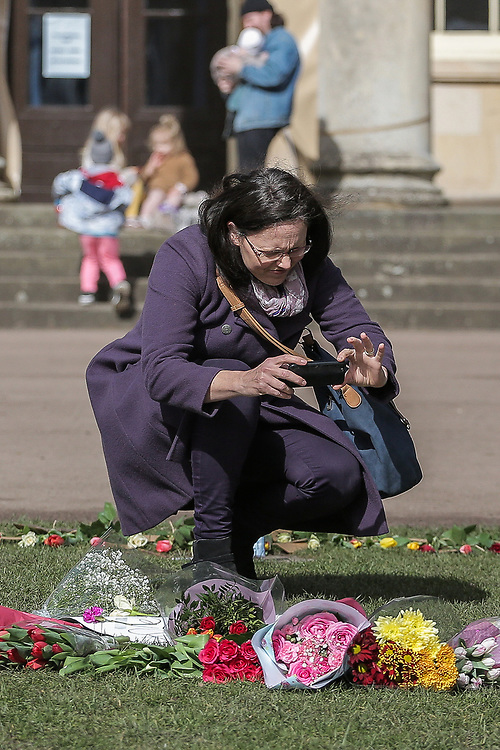 13th, March, 2021. Cheltenham, England. A woman takes a photograph of the flower collection in memory of Sarah Everard.