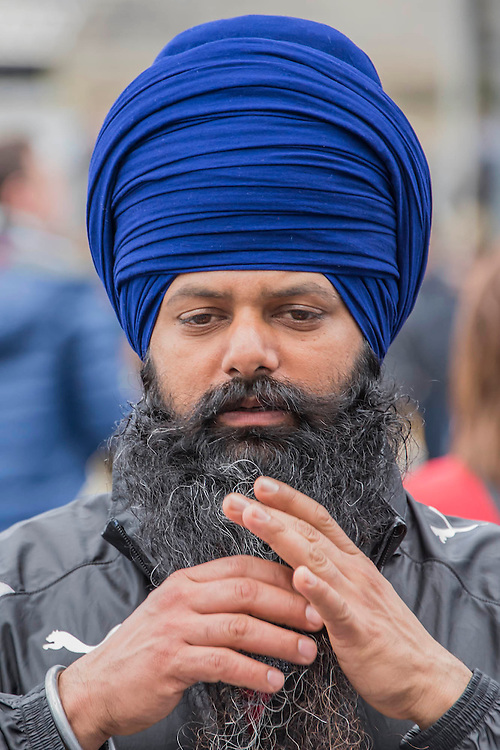A man adjusts his substantial beard - The Vaisakhi Festival at City Hall and More London Riverside on Saturday 9 April, celebrating the holiest day of the Sikh calendar. This year's celebrations will take place just before the official Vaisakhi festival on 13 April which commemorates the beginning of Sikhism as a collective faith and London's celebrations are an opportunity for people from all communities, faiths and backgrounds to experience a festival that is celebrated by over 126,000 Sikhs who live in the capital and 20 million people across the world.