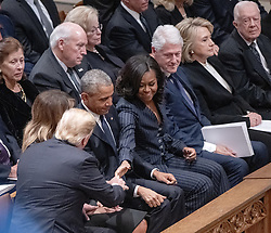 United States President Donald J. Trump reaches out to shake hands with former first lady Michelle Obama as he and first lady Melania Trump arrive for the National funeral service in honor of the late former United States President George H.W. Bush at the Washington National Cathedral in Washington, DC on Wednesday, December 5, 2018. At top right are former US President Bill Clinton, former US Secretary of State Hillary Rodham Clinton, former US President Jimmy Carter.<br /> Photo by Ron Sachs / CNP/ABACAPRESS.COM