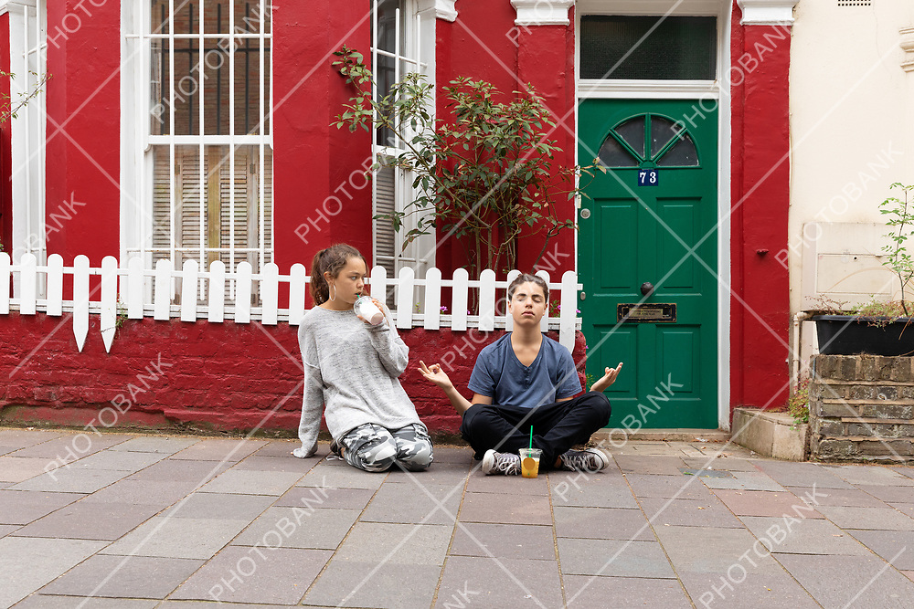 Young boy is sitting outside with his legs crossed doing yoga and the girl looks at him strangely. Urban context.
