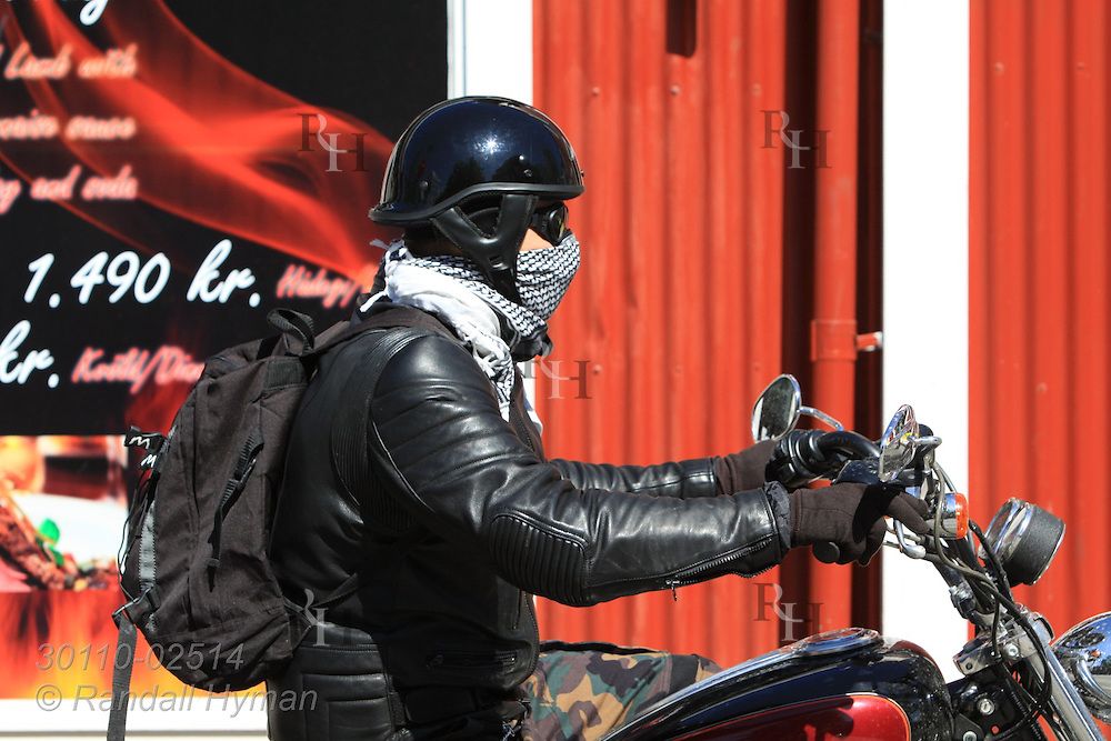 Motorcyclist wears makeshift dust mask as he prepares for motorbike tour on country roads; Reykjavik, Iceland.