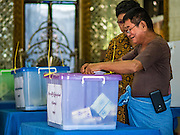 08 NOVEMBER 2015 - YANGON, MYANMAR:  A man drops his ballot into a ballot box in his polling place in a Buddhist temple in North Okkalapa, a township outside central Yangon. The citizens of Myanmar went to the polls Sunday to vote in the most democratic elections since 1990. The National League for Democracy, (NLD) the party of Aung San Suu Kyi is widely expected to get the most votes in the election, but it is not certain if they will get enough votes to secure an outright victory. The polls opened at 6AM. In Yangon, some voters started lining up at 4AM and lines were reported to long in many polling stations in Myanmar's largest city.     PHOTO BY JACK KURTZ