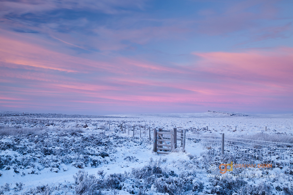 Dawn skies glow pink above a snow covered Burbage Moor and a distant Stanage Edge. A snow-covered winter landscape scene in the Peak District. England, UK.
