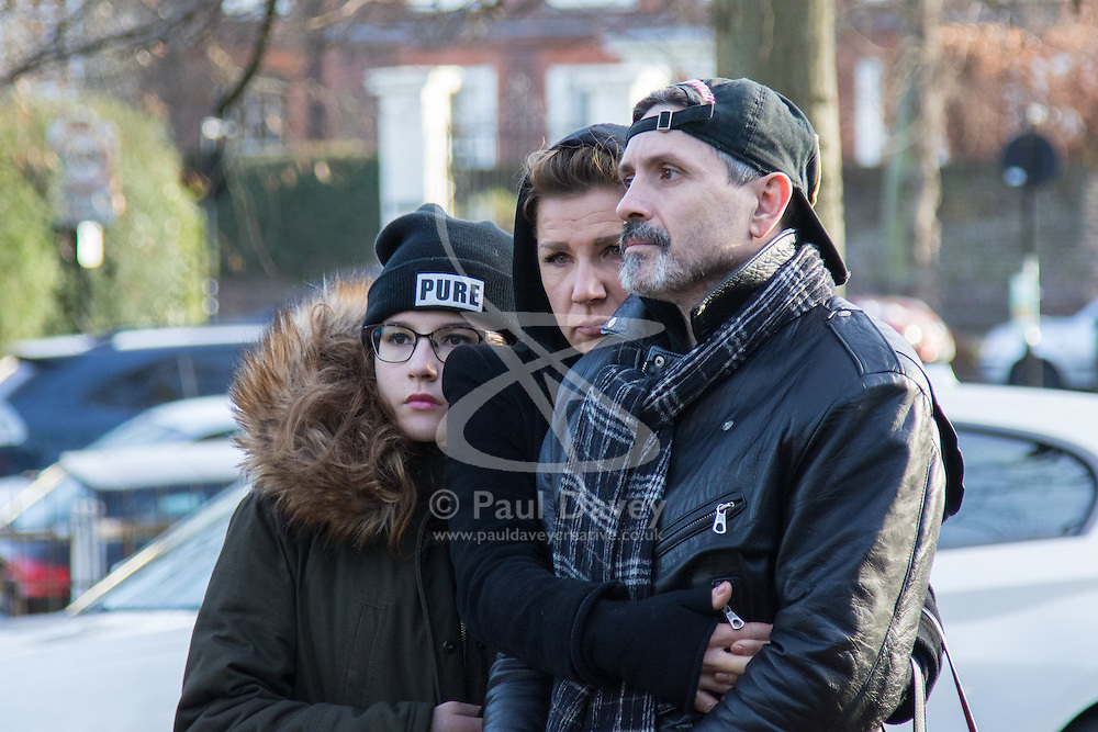 Highgate, London, December 26th 2016. Fans gather outside the London home of pop icon George Michael who died on Christmas day. PICTURED: A family grief-stricken embrace each other after laying flowers.
