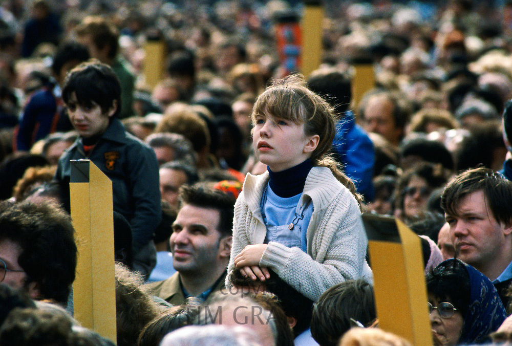 Child among crowd of pilgrims gathered in Paris for visit by Pope John Paul II to France