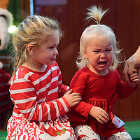 HARRISBURG, PA:  Avery, 4, consoles her sister, Delaney Drew, 1, as they greet Santa who sits behind plexiglass due to the coronavirus (COVID-19) pandemic, at a Bass Pro Shop's Outdoor World in Harrisburg, PA on December 12, 2020. The pandemic has forced difficult decisions about maintaining the holiday tradition of visits to Santa Claus versus safety concerns.  Plexiglass dividers, face shields, and physical distancing are among the precautions for those locations that have proceeded with Santa photo opportunities.  CREDIT:  Mark Makela for The New York Times
