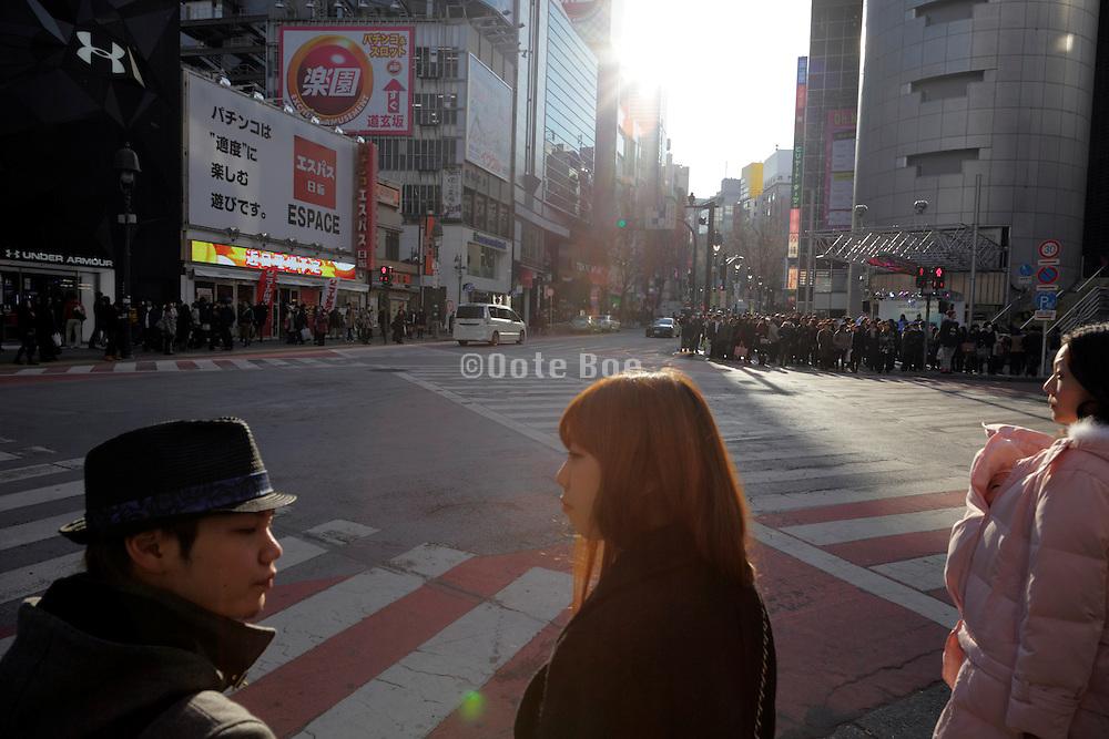 people waiting at pedestrian street crossing Tokyo Japan