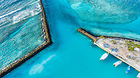 Aerial view of the harbour entry of local / inhabited island Vashafaru, Haa Alif Atoll, Maldives, Indian Ocean with crashing waves, reef and boats / dhonis anchored