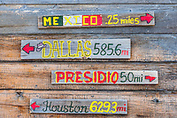 Signs in Lajitas (on the Rio Grande River near Big Bend National Park), Texas USA point to different cities in Texas. Mexico is a 1/4 of a mile away (on the far side of the Rio Grande).
