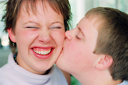 Teenage boy with Downs Syndrome kissing sister on cheek,