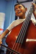 09/10/12 SJ - Douglas Perez tries out a bass while enrolling in El Sistema student orchestra at the Edgerly School, Sept. 10, 2012.<br /> Wicked Local staff photo by Kate Flock