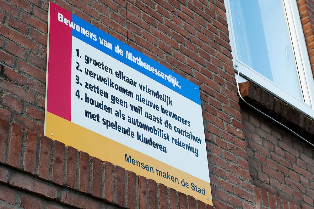 Nederland, Rotterdam, 2 jan 2013.Op de gevel van de woningen aan de Mathenesserdijk hangen borden met gedragsregels voor buurtbewoners. Dat men elkaar vriendelijk groet, geen vuilnis naast de container zet, rustig rijdt. De bedoeling is dat men vriendelijk met elkaar omgaat en dat de buurt daardoor leuker wordt voor iedereen..Foto(c): Michiel Wijnbergh
