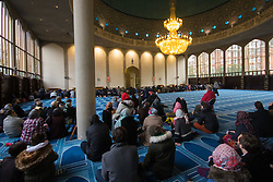 Regents Park Mosque, London, February 5th 2017. Dozens of curious non-Muslims are welcomed at Regent's Park Mosque in London as part of the Muslim Council of Britain's annual 'Visit My Mosque Day'. Visitors were able to observe prayers and we shown around the mosque by members, where there was a exhibition of the history and teachings of Islam. PICTURED: Visitors observe prayers in the Men's Prayer Hall.