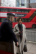 Two people with mobile phones hold a physical conversation on the street, on 11th April, 2018, in London, England.