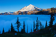Thick fog covers a high mountain valley that reaches up to Mount Baker, a 10,781 foot (3,286 meter) volcano located in the North Cascades of Washington state. Valley fog, which is a type of radiation fog, can be incredible dense. It forms when air along ridgetops and mountain slopes cools after sunset. The air then becomes dense and sinks into the valley below where it continues to cool and becomes saturated, causing fog to form.