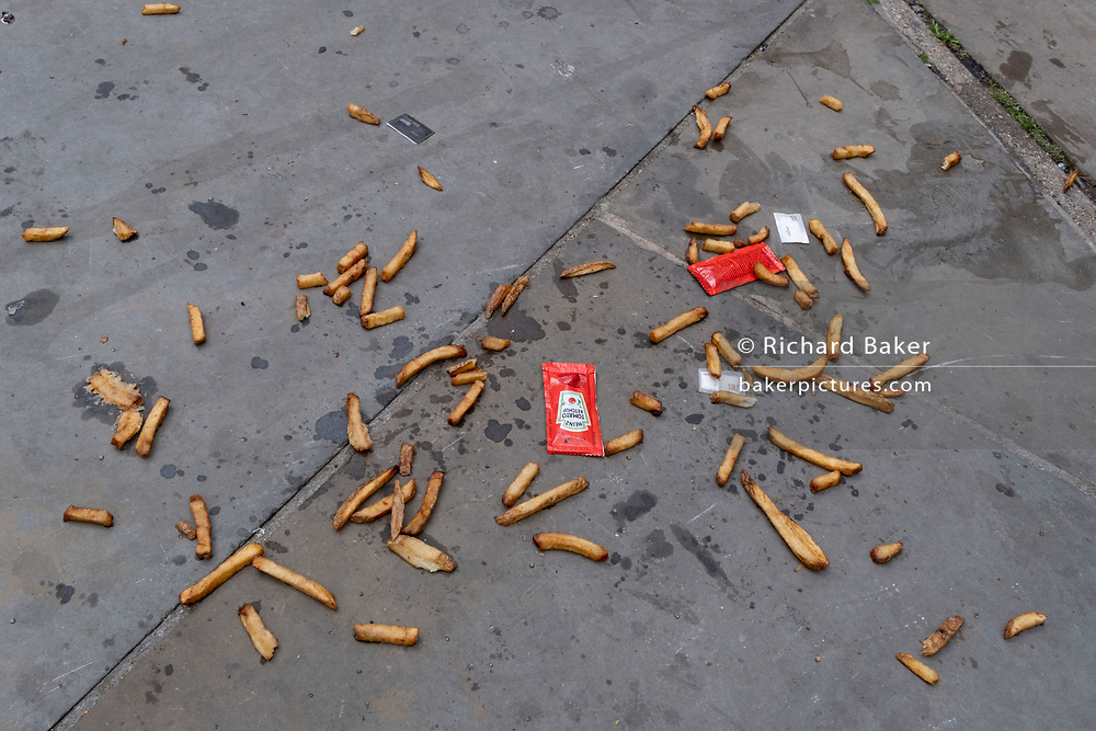 Along with sachets of salt and tomato ketchup, the remains of a portion of chips (aka French Fries) lie scattered on the pavement on London's Southbank, on 10th June 2021, in London, England. (Photo by Richard Baker / In Pictures via Getty Images)