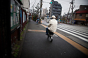 TOKYO, JAPAN - 19 MARCH - Shinagawa  - a Man riding fastly a mini motor bike on the sidewalk. March 2012