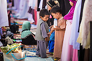 28 JULY 2014 - KHLONG HAE, SONGKHLA, THAILAND: A child walks between lines of adults during Eid services at Songkhla Central Mosque in Songkhla province of Thailand. Eid al-Fitr is also called Feast of Breaking the Fast, the Sugar Feast, Bayram (Bajram), the Sweet Festival and the Lesser Eid, is an important Muslim holiday that marks the end of Ramadan, the Islamic holy month of fasting.   PHOTO BY JACK KURTZ