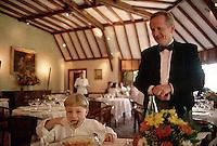 ca. September 1997, Saulieu, France --- Hubert Couilloud, maitre d'hotel at Bernard Loiseau's Cote d'Or restaurant, watches as a young boy eats. --- Image by © Owen Franken/CORBIS
