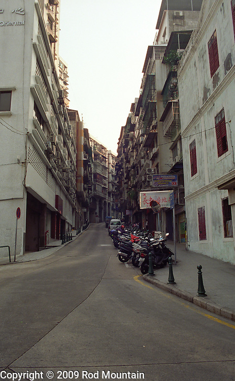 Motorcycles and Mopeds make up for most of the rides parked on narrow side street in Macau, China.