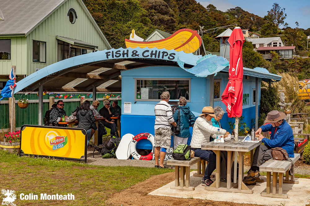 Tourists enjoy lunch, Kai Kart fish and chips caravan, Oban, Rakiura, Stewart Island.