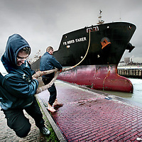 Nederland, IJmuiden , 3 december 2009..Bij IJmuiden moeten de schepen door een sluizencomplex dat in totaal uit vier sluizen bestaat. De grootste ervan is de Noordersluis, die voor steeds meer vracht- en cruiseschepen vanwege hun omgang de enige toegangspoort is tot de Amsterdamse haven. De Noordersluis stamt uit 1929..Op de foto wordt een vrachtschip  de sluis in begeleidt en  de touwen aan de kade vastgebonden...Foto:Jean-Pierre Jans
