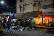 A rickshaw rider holds his nose as he passes an overflowing rubbish bin at night near the Moghbazar Mouchak Flyover in the Tejgaon industrial area on the 23rd of September 2018 in Dhaka, Bangladesh.