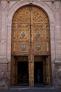 Wooden door on Morelia Cathedral on the Plaza de Armas Morelia, Michoacan state Mexico. The city is a UNESCO World Heritage Site and hosts on of the best preserved collection of Spanish Colonial architecture in the world. Commissioned by the Duke of Albuquerque, appointed Viceroy to the territories of Mexico, ordered its construction in 1660 which was carried out by the Italian master Vicente Barroso until his death in 1692 it took an additional 52 years to complete. The Cathedral has the highest and bulkiest church towers of the continent.