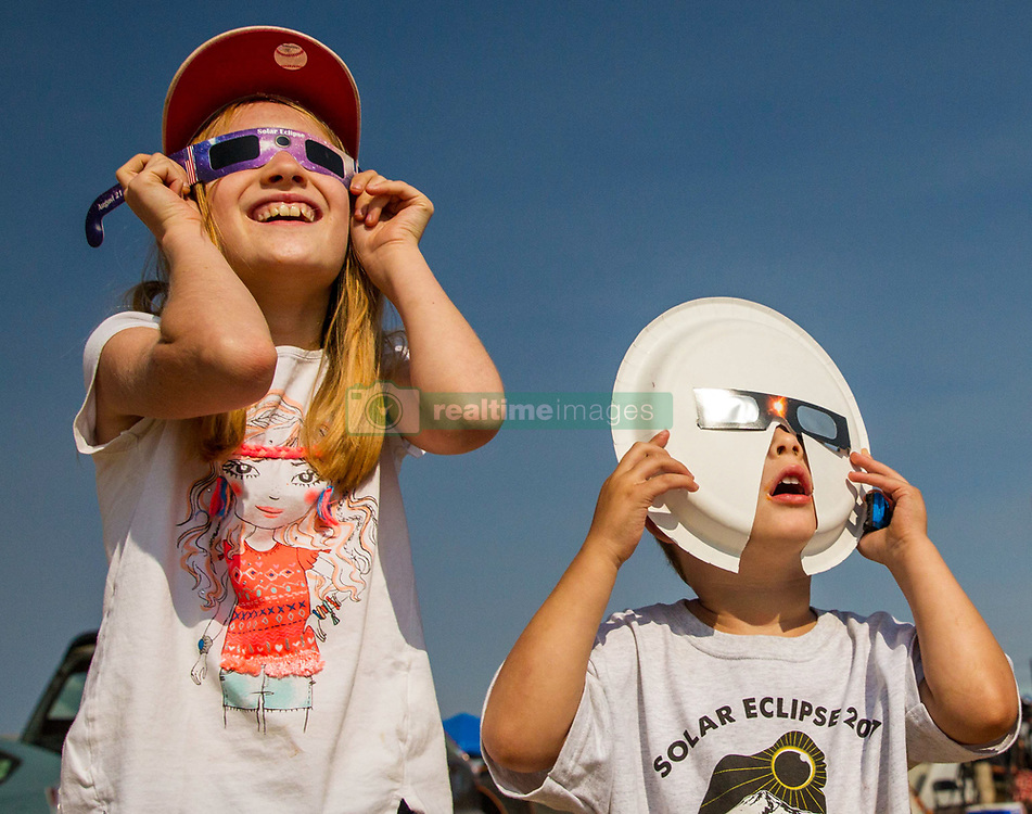 Molly Macclanahan, 8, and Lucas Witzel, 3, watch as the total solar eclipse nears totality at the Madras Municipal Airport on Monday, August 21, 2017. (Rhianna Gelhart/The Register-Guard)