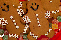 Closeup of gingerbread men arranged on glass plate with gumdrops.