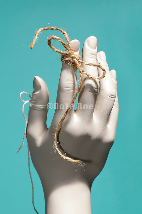 strings tied around female mannequin finger and thumb