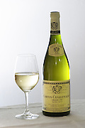A bottle of Maison Louis Jadot Bourgogne Corton Charlemagne Grand Cru 2003 white burgundy wine and a glass of white wine standing on a table top with a white cloth. Backlit backlight back light lit. white background, Maison Louis Jadot, Beaune Côte Cote d Or Bourgogne Burgundy Burgundian France French Europe European