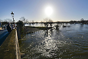 © Licensed to London News Pictures. 16/02/2014. Chertsey, UK. People look at the floodwater from Chertsey Bridge. An Aqua dam has been erected along Bridge Road in Chertsey, Surrey. At almost half a mile long and four feet high the dam is designed to protect 200 houses on the South Side of the street. The Environment Agency has said there is nothing they can do to protect the houses on the North side if flood water from the River Thames rises. . Photo credit : Stephen Simpson/LNP