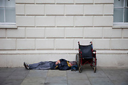 A homeless man lays next to his wheel chair sleeping, perhaps passed out on the pavement in Covent Garden, London.