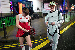 © Licensed to London News Pictures . 26/12/2018. Wigan, UK. A man wearing a cheerleader costume adjusts his underwear . Revellers in Wigan enjoy Boxing Day drinks and clubbing in Wigan Wallgate . In recent years a tradition has been established in which people go out wearing fancy-dress costumes on Boxing Day night . Photo credit: Joel Goodman/LNP