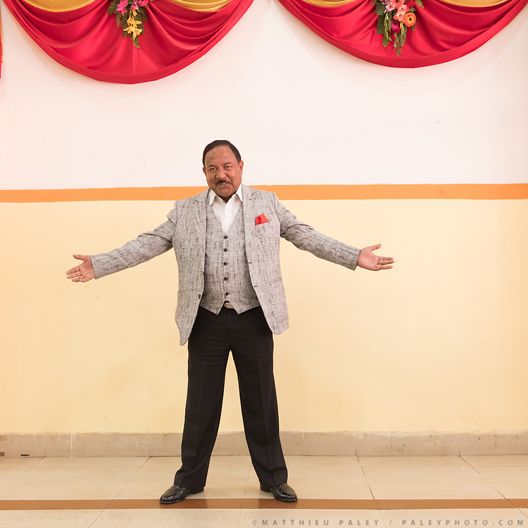 A wedding participant poses for a portrait, opening his arms, during the reception.