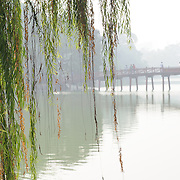 In the background at right, partly obscured by a thick morning haze, is The Huc Bridge (Morning Sunlight Bridge). The red-painted, wooden bridge joins the northern shore of the lake with Jade Island and the Temple of the Jade Mountain (Ngoc Son Temple).