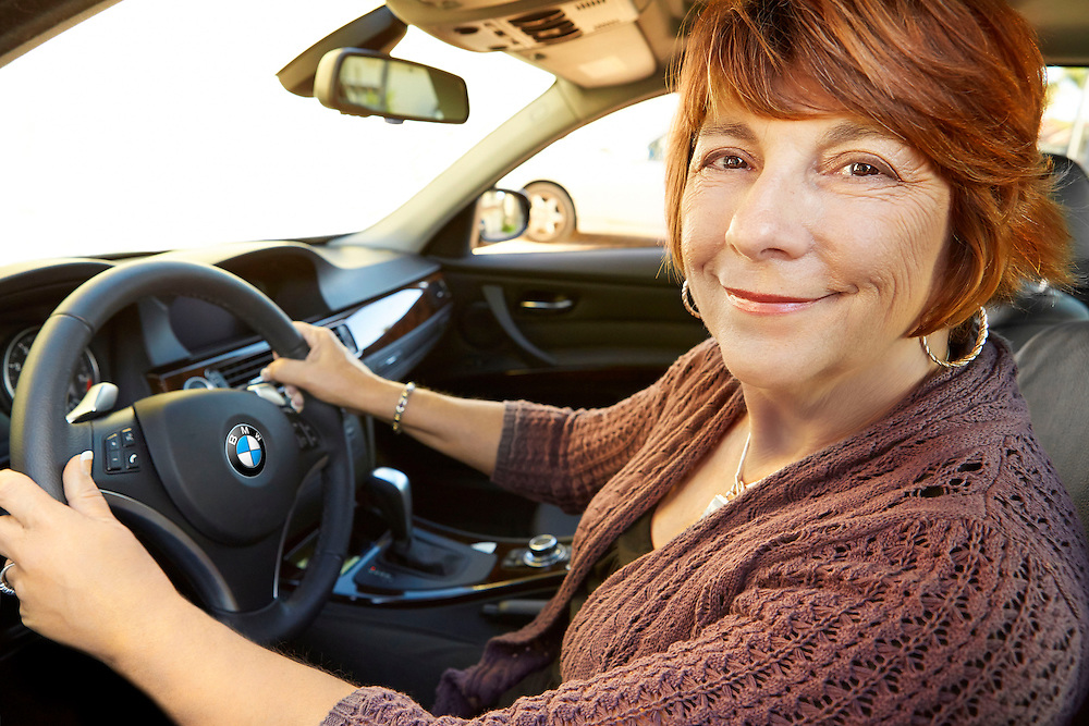 Portrait photograph of smiling woman in her 60s driving BMW sports car